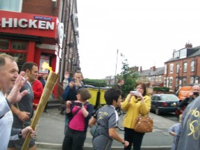 Olympic torch carrier headed down the streets of Leeds, England