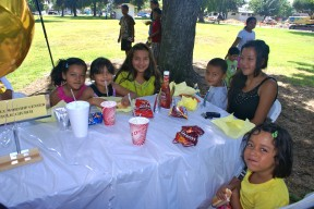 Children and families enjoy a barbecued hot dog meal before the school supply giveaway