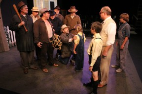 Scout's unwavering innocence breaks up a mob in a pivotal scene from Harper Lee's classic novel, To Kill a Mockingbird.  Pictured, from left, LARRY MATTOX, HENRY MONTELONGO, PATRICK ALLAN TROMBORG, JIM BROWN, GREG RUUD, MARK MCKEON, NOEL ADAMS, BAILEY SHORT, MARTY MARGOLIN, CHRIS CARSTEN, and COLIN CLARK-BRACEWELL.