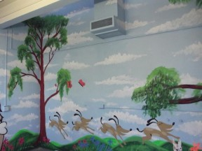 One of many walls being painted with murals.