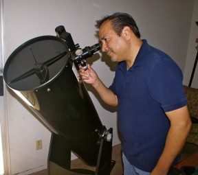"""Amateur astronomer, Fabian Barajas, looking through the eye piece of his 12"""" reflective telescope."""
